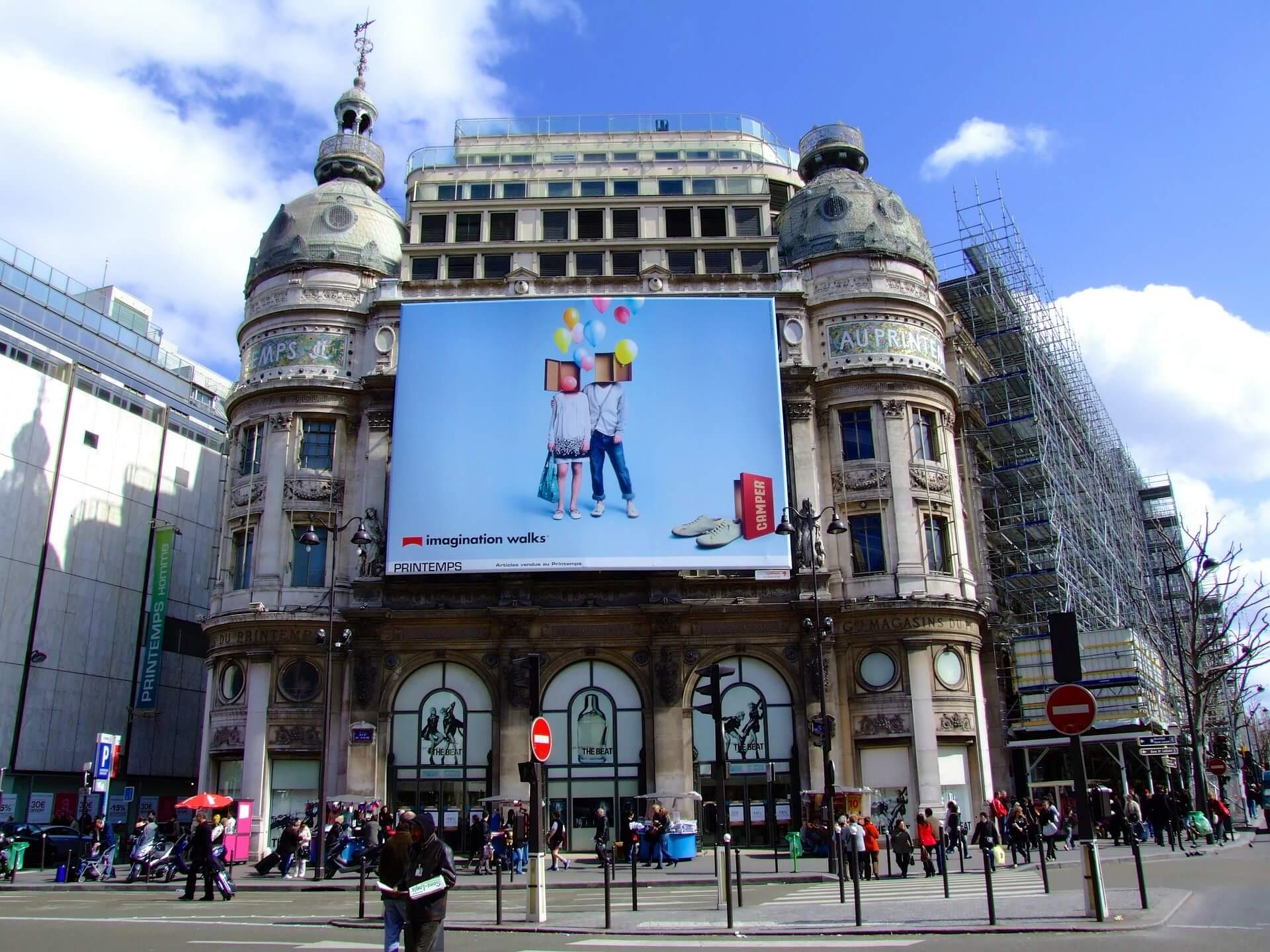 Plakatwerbung an einer Hauswand als beispiel für offline Marketing-Maßnahmen